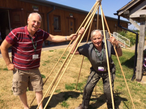 Two volunteers making a wigwam