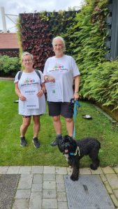 Two walkers and a dog with certificates after completing the Chester Business Club Charity Walk