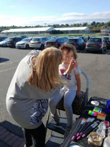 Child having face painted before Chester Business Club Charity Walk